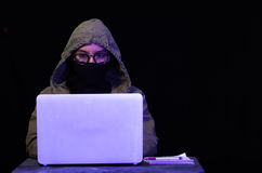 Portrait of hacker with laptop on dark background Royalty Free Stock Images