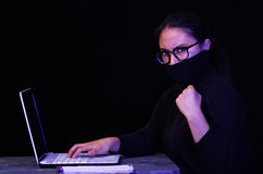 Portrait of a hacker with laptop on dark background using glases while she is working Stock Image