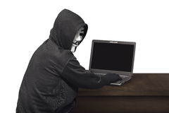 Portrait of hacker man with mask looking back while typing lapto Royalty Free Stock Photography