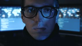Portrait of Hacker programmer in glasses looks at camera while blue code characters reflect on his face in cyber. Portrait of Hacker programmer in glasses looks stock video