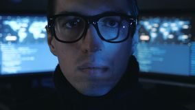 Portrait of Hacker programmer in glasses looks at camera while blue code characters reflect on his face in cyber. Portrait of Hacker programmer in glasses looks stock video footage