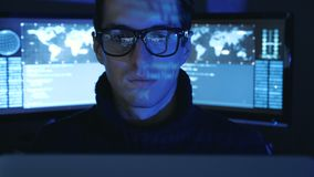 Portrait of Hacker Programmer in glasses looks at camera while blue code characters reflect on his face in cyber. Portrait of Hacker programmer in glasses looks stock footage