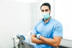 Portrait of an Dentist. Portrait of hadsome dentist doctor wears blue uniform and face mask, indoor shot in modern dentist office royalty free stock images
