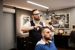 Hairdresser combing customer hair. Portrait of hairdresser combing customer hair Stock Photography