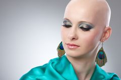 Portrait of hairless woman in turquoise silk dress. Beauty portrait of bald woman in turquoise silk dress Stock Photo
