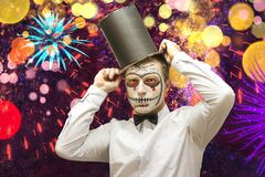 Portrait of Halloween man on festive party. Man with skeleton mask on face in black hat on colorful celebration background.  stock photography