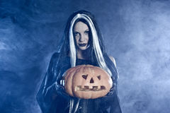 Portrait Halloween witch with a pumpkin Royalty Free Stock Photos