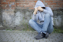 Portrait of handcuffed man with face hidden by sweatshirt hood Stock Photo