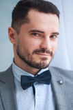 Portrait of a handsome adult man in a gray suit in the studio. The groom is waiting for the bride. Wedding Royalty Free Stock Image
