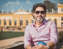 Portrait of a handsome adult man wearing sunglasses. And pink - red t-shirt, outdoors at summer Royalty Free Stock Image
