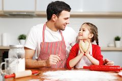 Portrait of handsome affectionate father embraces her little daughter, make cookies together, being in good mood. Domestic atmosphere. Baking concept. Friendly royalty free stock photos