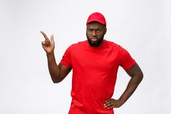Portrait of handsome african american delivery man annoying pointing finger on side. Isolated over grey background. Portrait of handsome african american stock photography