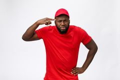 Portrait of handsome african american delivery man annoying pointing finger on side. Isolated over grey background. Portrait of handsome african american stock image