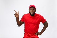 Portrait of handsome african american delivery man annoying pointing finger on side. Isolated over grey background. Portrait of handsome african american royalty free stock images