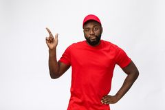 Portrait of handsome african american delivery man annoying pointing finger on side. Isolated over grey background. Portrait of handsome african american stock photos
