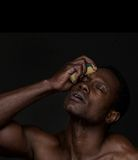 African American Man Washing Face. Portrait of a handsome african american man washing face Stock Photography