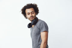 Portrait of handsome african man with headphones over white background. Copy space. Royalty Free Stock Photo