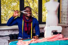 Portrait of a handsome african man smiling seamstress with sewing machine.Afrio American man stylish designer working in