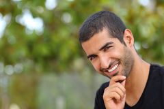 Portrait of a handsome arab man face outdoors. In a park with a green background Stock Image