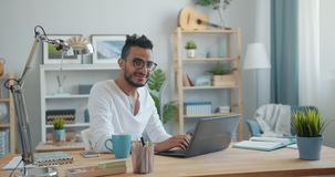 Portrait of handsome Arab using laptop at home then smiling looking at camera. Portrait of handsome young Arab using laptop at home then smiling looking at stock footage