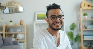 Portrait of handsome Arabian guy in glasses looking at camera indoors at home. Portrait of handsome young Arabian guy in glasses looking at camera indoors at stock video footage