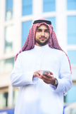 Portrait of a handsome arabian man using a smart phone stock photo