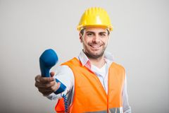 Portrait of handsome architect handing telephone receiver. And smiling on gray background Stock Photography
