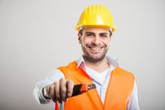 Portrait of handsome architect holding cutter tool. And smiling on gray background stock images