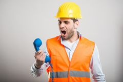Portrait of handsome architect screaming at telephone. And smiling on gray background Royalty Free Stock Images