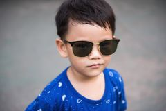 Attractive Asian boy with sunglasses. Portrait of handsome Asian boy with sunglasses with copy space for text. Attractive Little child fashion Royalty Free Stock Photography