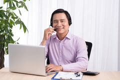 Portrait of handsome asian hotline person consultant wearing headset royalty free stock image