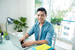 Portrait of handsome asian young business man working on laptop Stock Photography