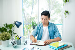 Portrait of handsome asian young writing something on notebook a Royalty Free Stock Photography