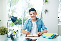 Portrait of handsome asian young writing something on notebook a Stock Photography