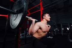 Portrait of a handsome athlete at gym. man does the exercise with  barbell, standing and squatting. big confident Stock Photo