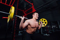 Portrait of a handsome athlete at gym. man does the exercise with  barbell, standing and squatting. big confident Royalty Free Stock Photos
