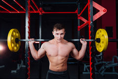 Portrait of a handsome athlete at gym. man does the exercise with  barbell, standing and squatting. big confident Royalty Free Stock Photo