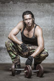 Portrait of handsome athlete during his workout rest. Handsome muscle man wearing camouflage pants Royalty Free Stock Photography
