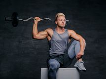 Portrait of a handsome, athletic blond male holds barbell on his shoulder. Portrait of a handsome, athletic blond male sits on a white box and holds barbell on Stock Photos