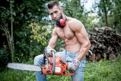 Portrait of handsome athletic man with chainsaw and protective Stock Photography