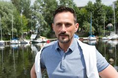 Portrait of handsome atractive businessman near of river with boats. River cruise for successful men. Portrait of handsome happy man near of river with boats Stock Photo