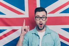 Portrait of handsome attractive guy with stubble in glasses show. Ing index finger up, find a solution, have an idea with opened mouth over English flag Royalty Free Stock Photos