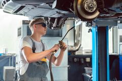 Portrait of a handsome auto mechanic looking at camera with confidence. Portrait of a young and handsome auto mechanic looking at camera with confidence while Royalty Free Stock Images