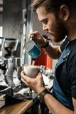 Barista Cafe Making Coffee Preparation Service Concept. Portrait of a handsome barista making a cup of coffee at the coffee shop Royalty Free Stock Images