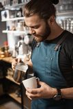 Barista Cafe Making Coffee Preparation Service Concept. Portrait of a handsome barista making a cup of coffee at the coffee shop Stock Photos