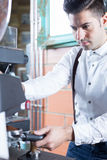 Portrait of handsome bartender grinding coffee Stock Photography