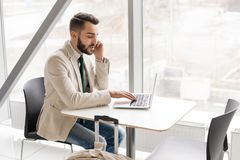 Handsome Businessman Working in cafe. Portrait of handsome bearded businessman speaking by phone and using laptop sitting at table against window in modern Royalty Free Stock Photography
