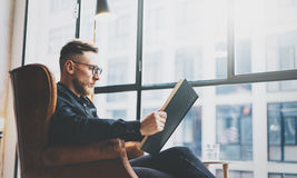 Portrait handsome bearded businessman wearing glasses,black shirt.Man sitting in vintage chair modern loft studio, reading book an Stock Photography