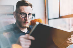 Portrait handsome bearded businessman wearing glasses,black shirt.Man sitting in vintage chair modern loft studio, reading book an Stock Image