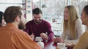Portrait of handsome bearded caucasian man talking with group of friends in cafe and smiling. Positive young man telling